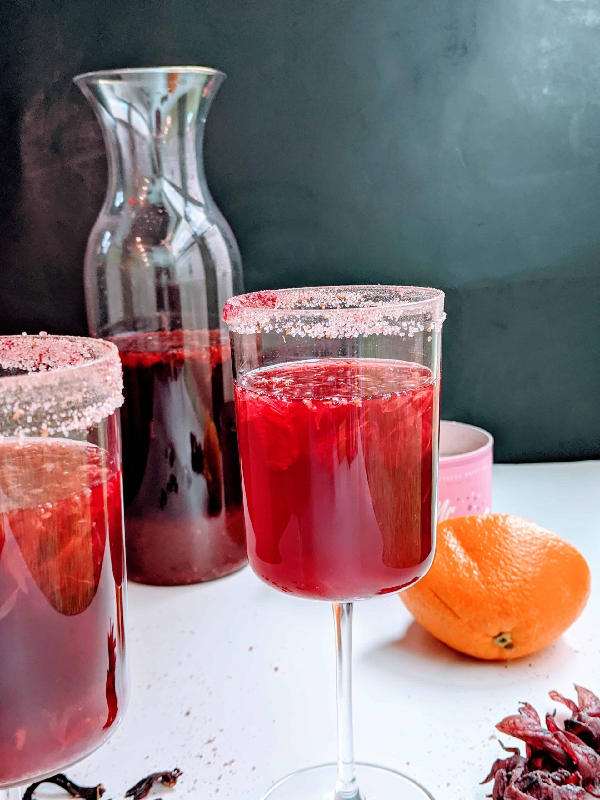 orange hibiscus cooler in wine glasses with a carafe