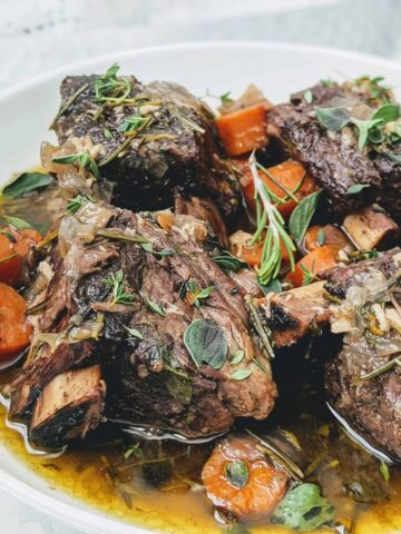 Herby Braised Short Ribs with carrots on a white plate