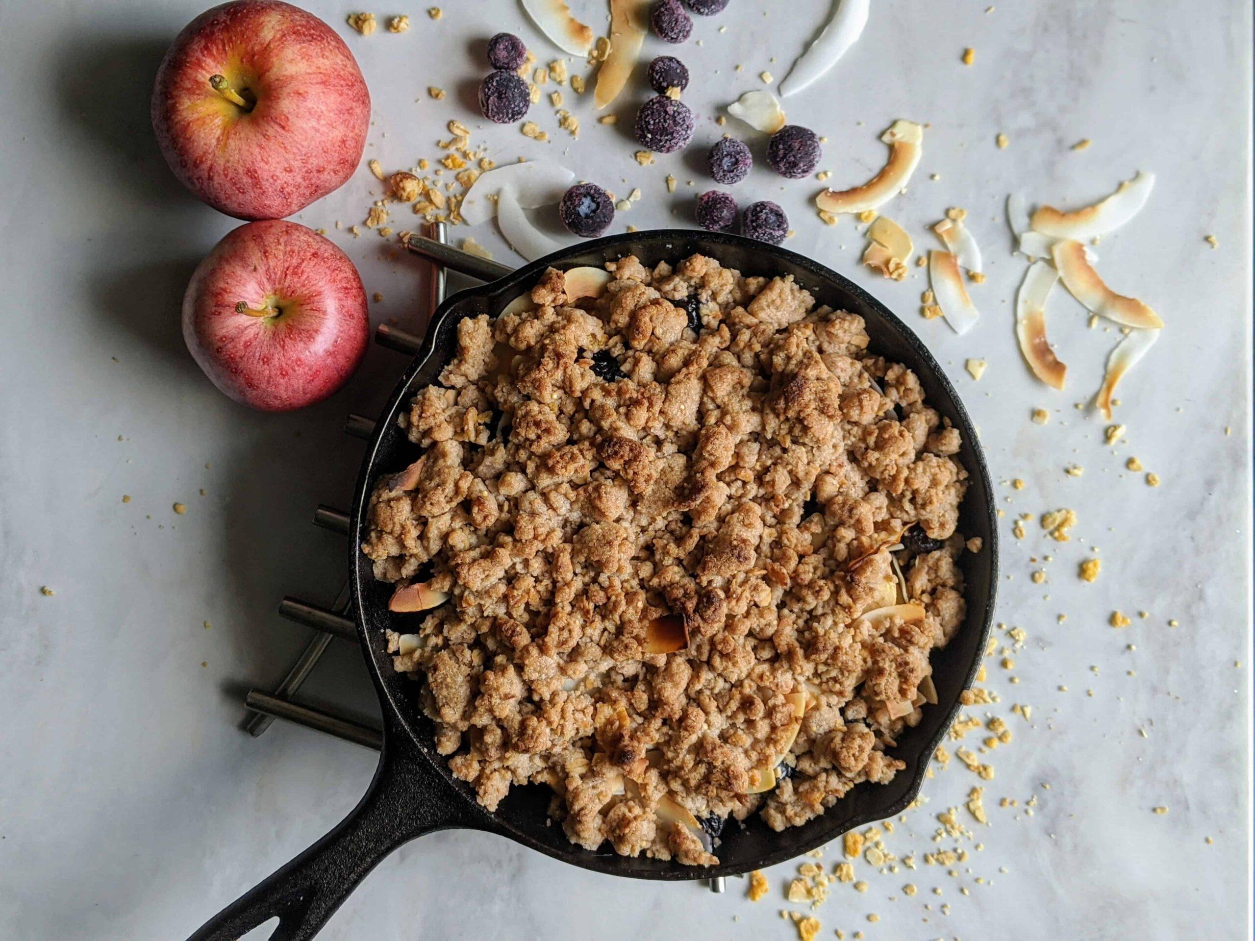 Coconut Crunch Blueberrry Spple Crisp in a cast iron pan