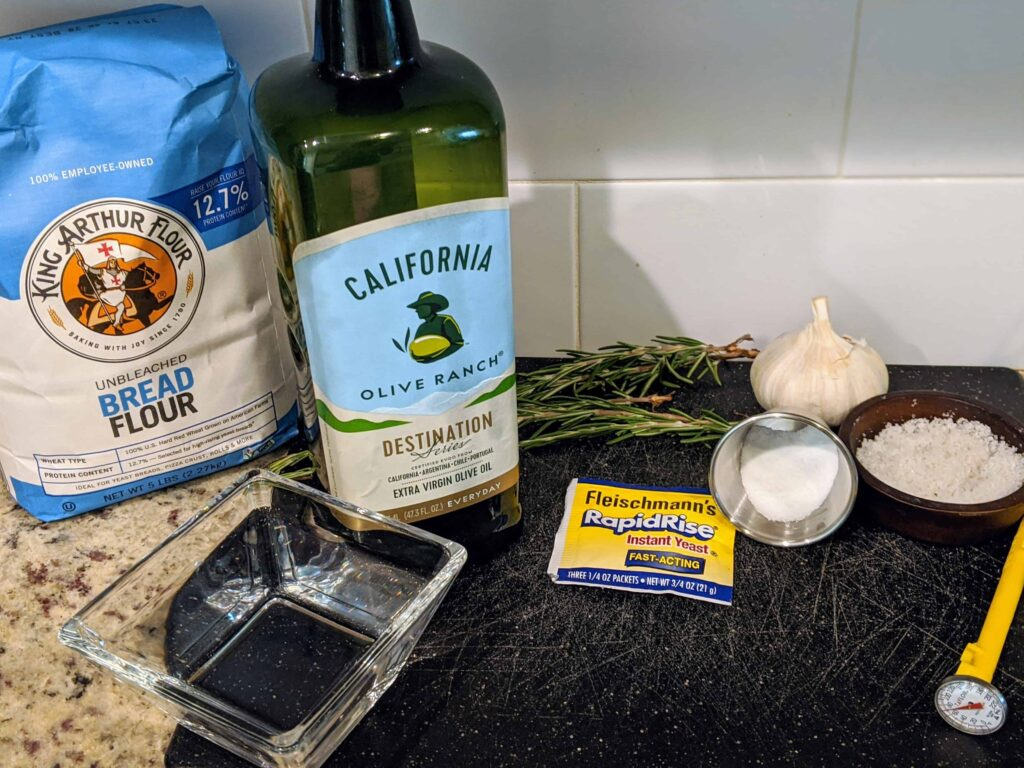bread flour, olive oil. yeast, garlic, herbs, thermomter, water on a black cutting board