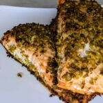 olive crusted baked salmon on a white plate