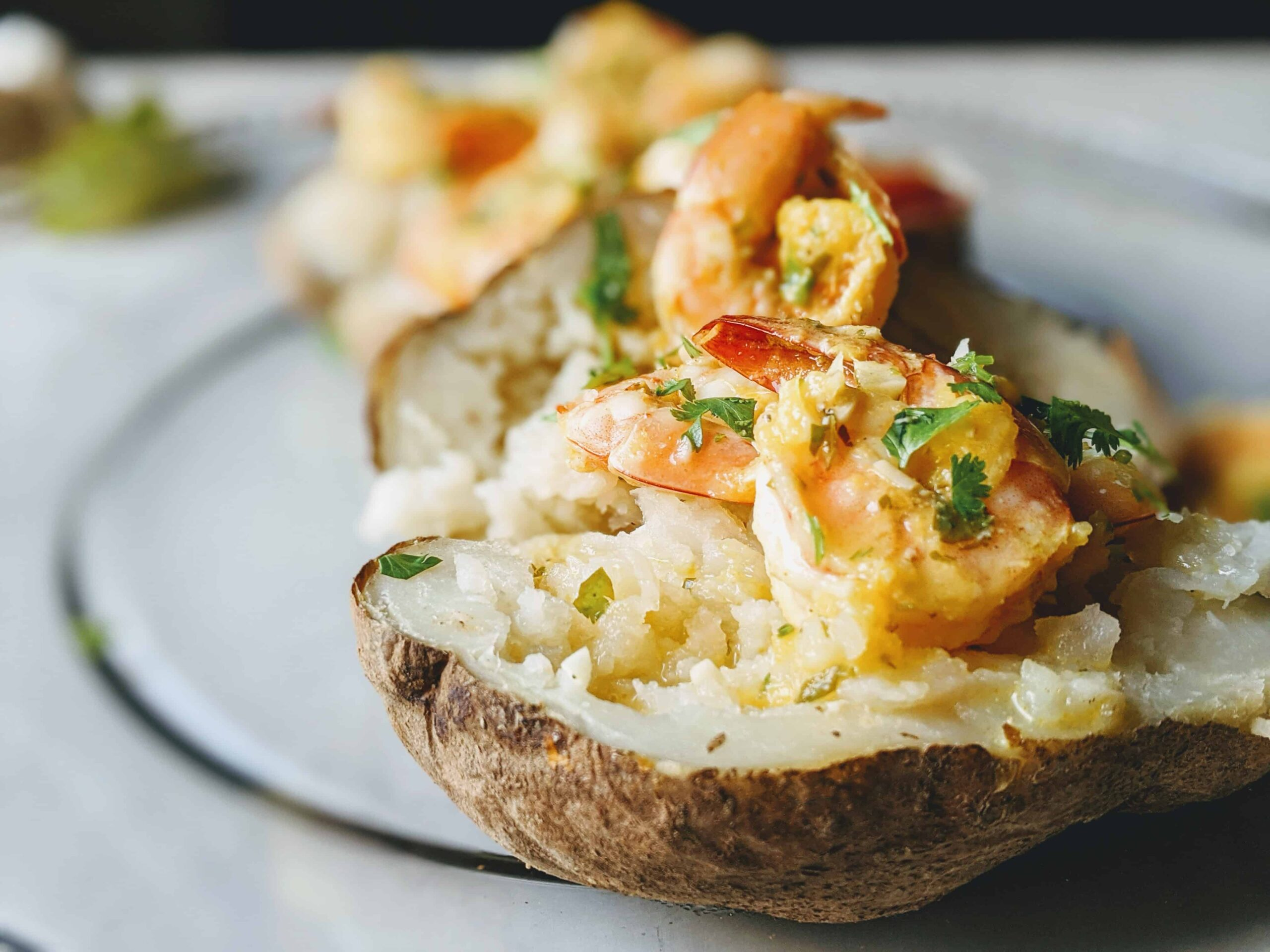 mojo shrimp baked potatoes on a clear plate