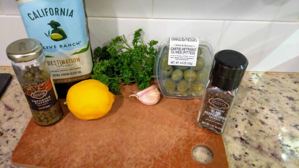 ingredients for olive tapenade on a cutting board