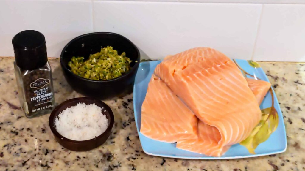 salmon, olive tapenade, salt and pepper on a counter