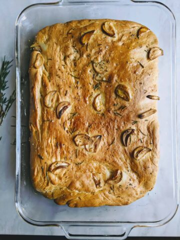 garlicky rosemary foccacia bread in a clear baking dish