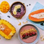 smoothie bowls 4 ways inside of fruit and different colored bowls