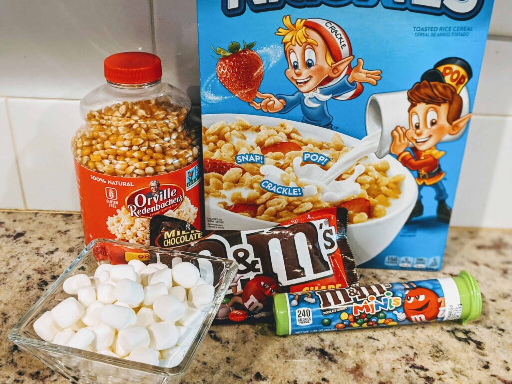 oppcorn, m&m's, rice krispies cereal, marshmallows on a counter