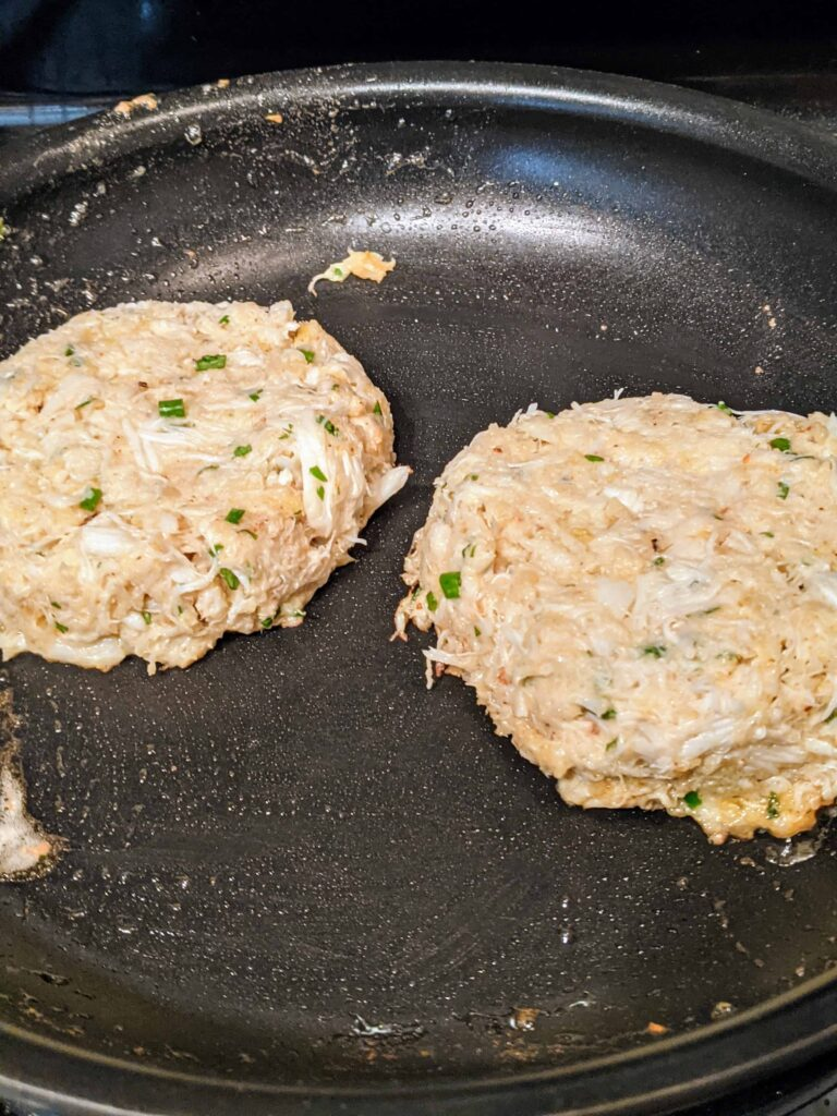 crabcakes cooking in a black pan