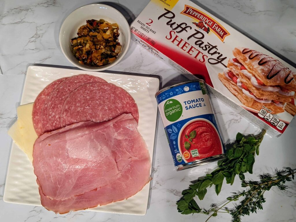 puff pastry, sliced meats, fresh herbs, tomato sauce, puff pastry, bell pepper and onions