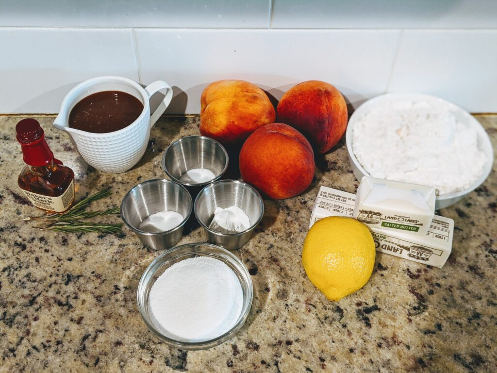 peaches, butter, lemon, rosemary, dry ingredients on a counter